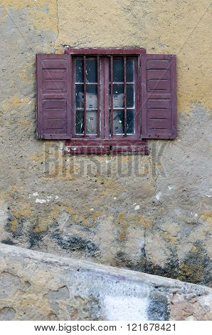 Old dirty window with magenta wooden shutters on old dirty wall