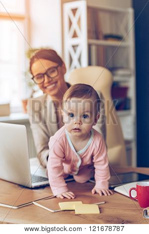Modern working mother. Little baby girl looking at camera while crawling on her mothers place of work