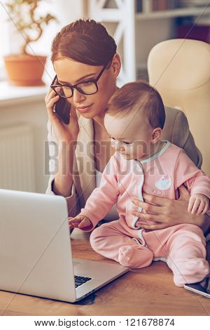Working with baby. Young beautiful businesswoman talking on mobile phone and looking at laptop while sitting with her baby girl at her working place