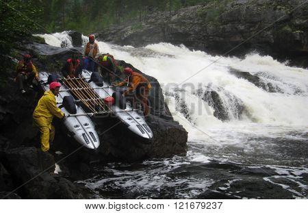 KOLA PENINSULA RUSSIA - AUGUST 12 - Men transfer inflatable catamaran on land because dangerous waterfall in Kola Peninsula on August 12 2008.