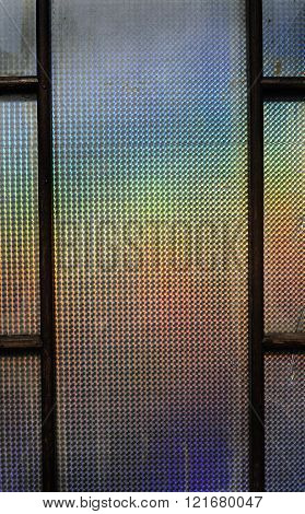 The sun reflecting off a prismatic window creating a multi colored rainbow background.