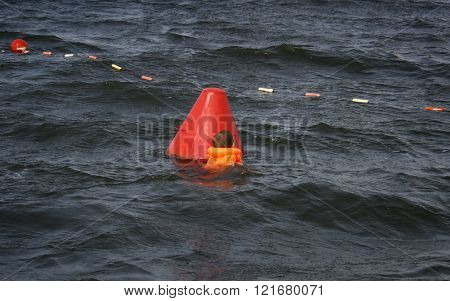 Little child in the life jacket near buoy