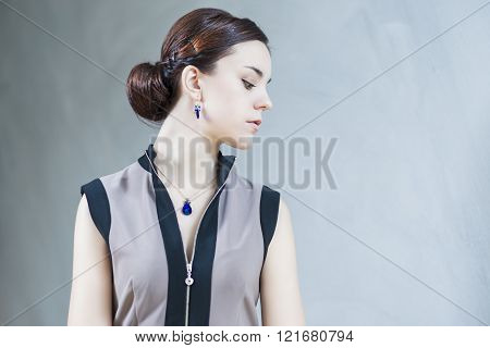 Portrait Of Sensual Brunette Female With Blue  Pendent And Earring Against Gray Wall