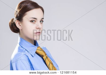 Sensual Caucasian Brunette Business Woman In In Official Blue Shirt And Orange Tie. Posing Against W