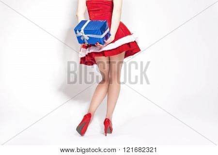 Celebration Concept And Ideas. Sexy Legs Of Caucasian Female Holding Christmas Gift Behind Her Back.