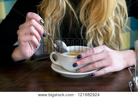 Woman Drink Tea In A Cafe And Hold A Spoon