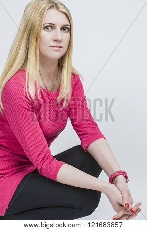Nice Caucasian Blond Woman In Pink Dress Posing Against White.