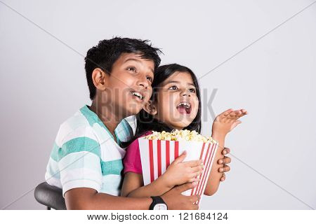 indian cute girl and boy eating popcorn, asian kids and popcorn, Little girl and little boy enjoy ea