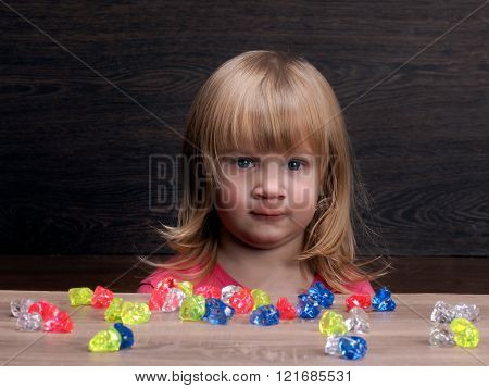 The child, a girl plays with colorful stones