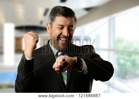 Mature hispanic businessman celebrating inside an office building