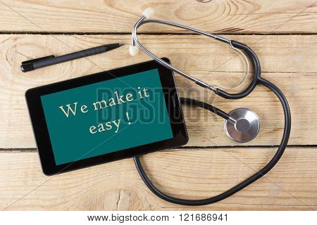 We make it easy - Workplace of a doctor. Tablet, medical stethoscope, black pen on wooden desk backg