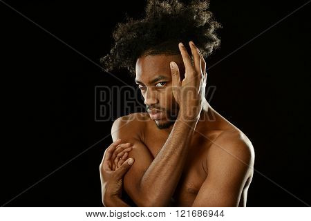 Portrait of young black man with nude torso on a dark background