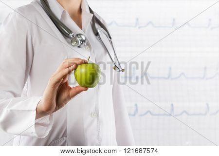 Healthcare and medicine concept - Female doctor's hand holding green apple. Close up shot on grey