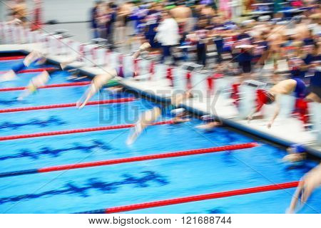 Motion blurred image of people diving into the pool at the start of a swimming race