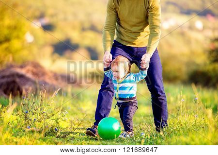 Father holding hands of his son making first steps