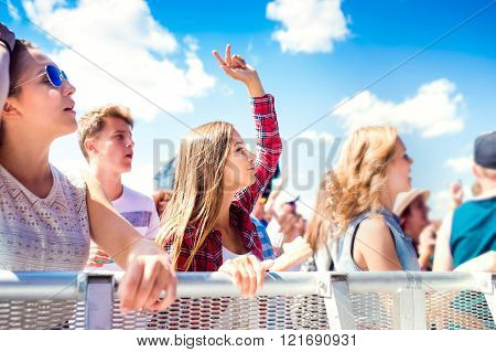 Teenagers at summer music festival dancing and singing