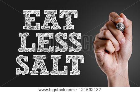 Hand writing the text: Eat Less Salt