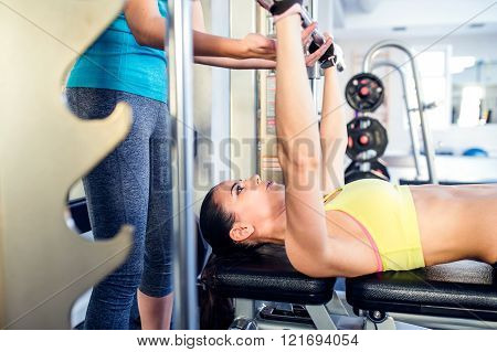 Woman with personal trainer bench pressing with weights, gym