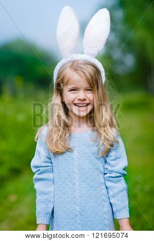 Outdoor Portrait Of Beautiful Smiling Little Girl With Long Blond Hair Wearing Rabbit Or Bunny Ears