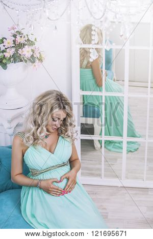 Beautiful Young Pregnant Woman In Fashionable Dress In A Interior