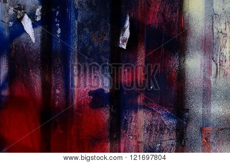 Dramatic grunge painted dark blue and red rusty garage door with torned paper pieces - creative background for your design