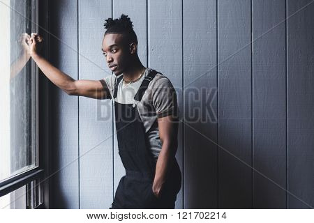Portrait of a young afroamerican indoors wearing a jumpsuit, looking outside through a window