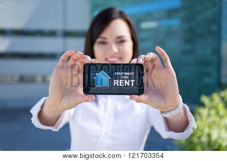Beautiful Business Woman Showing Phone With Real Estate Application