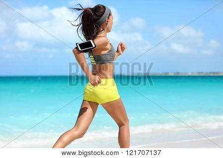 Fit woman cardio training doing running workout on beach. Unrecognizable athlete runner jogging fast on summer ocean background wearing a phone armband holder for music listening on smartphone app.