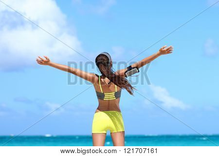 Winning carefree woman runner expressing happiness on beach summer vacation. Back view of happy female athlete showing freedom and success from fitness goal achievement. Weight loss concept.