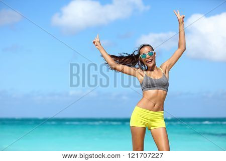 Happy cheerful fitness woman in sunglasses winning arms up doing v hand signs. Fit girl with slim body on sunny beach with raised arm showing peace sign in happiness of weight loss after workout.