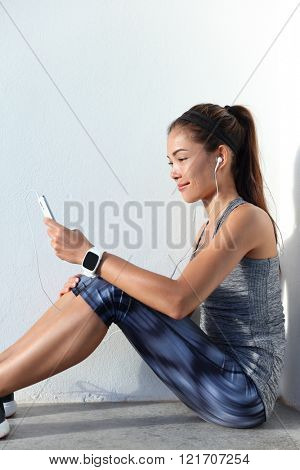Fitness girl choosing music motivation for workout listening to phone app and wearing wearable tech smartwatch watch. Female crossfit athlete relaxing getting ready for training using sport gadgets.