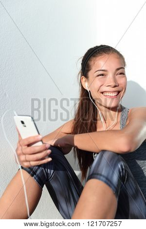 Happy active girl listening to music on smartphone app phone lifestyle. Young female athlete getting ready for fitness workout or running by choosing song playlist on phone smiling.