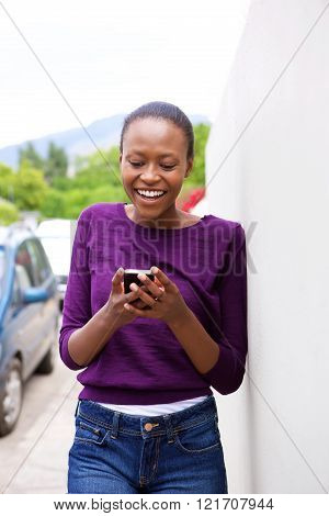 Happy African Woman Leaning Against Wall Looking At Cell Phone