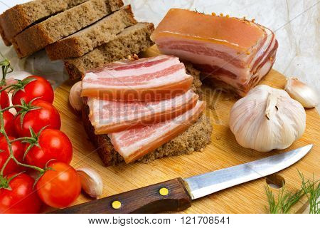 Splitting Salty Bacon With Cherry Tomatoes.