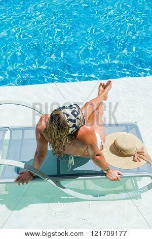 womansuntanning  enjoying on sunbed at swimming pool
