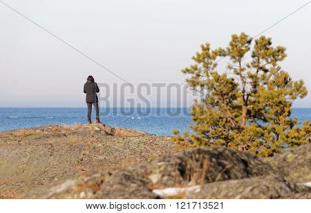 Silhouette of a thoughtful woman looking at the sea