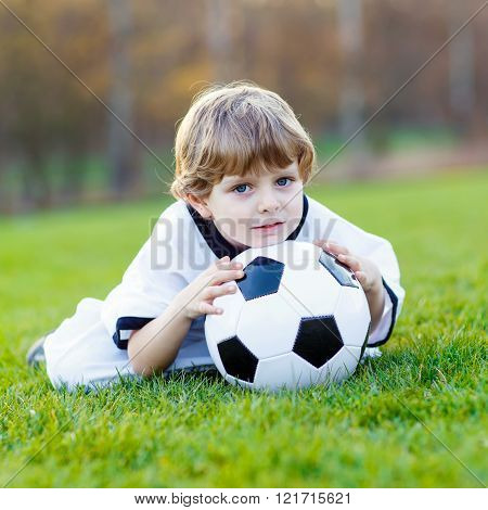 Kid boy playing soccer with football
