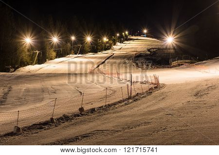 Night skiing on a snowy night with lights, two separated ski slopes and infrastructure at night