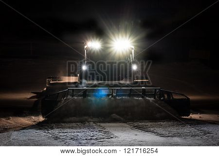 Snowcat preparing a slope at night in high mountains at skiing resort