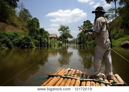CHIANG MAI, THAILAND - APRIL 23: A bamboo raft and his handler negotiates the meandering river downstream. April 23, 2009 in Thailand.
