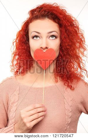 Red-haired young woman holding paper heart near mouth, isolated on white