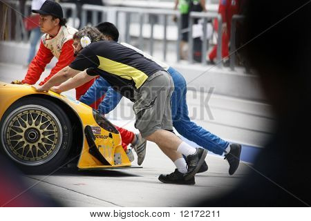SEPANG, MALAYSIA - AUGUST 8: Mechanics return the car into garage at the 12 hour race of the 2009 Merdeka Millennium Endurance Race August 8, 2009 in Sepang, Malaysia.