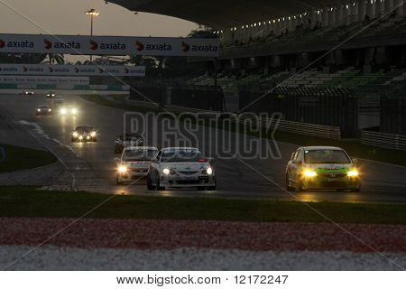 SEPANG, MALAYSIA - AUGUST 8: Cars on the track at dusk at the 2009 Merdeka Millennium Endurance Race August 8, 2009 in Sepang, Malaysia.