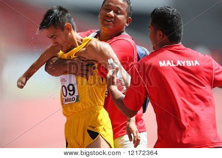 KUALA LUMPUR - AUGUST 15: Malaysia's amputee athlete Ahmad Rafie (L) after winning the 100m track and field event of the fifth ASEAN Para Games on August 15, 2009 in Kuala Lumpur.