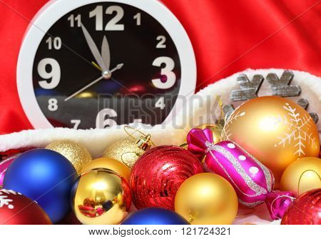 Clock and christmas balls and toys in a red bag