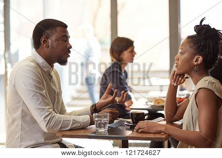 Handsome African businessman discussing his entrepreneurial idea with a respected African businesswoman in a busy and modern cafe