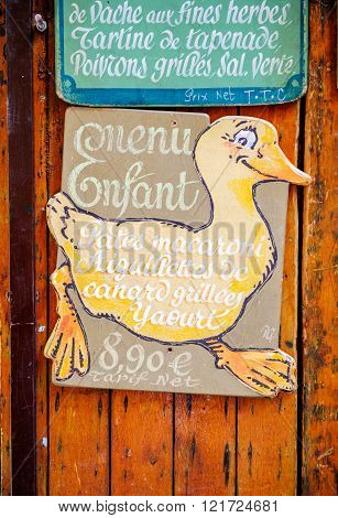MARSEILLE FRANCE - JUL 18 2014: Funny old vintage goose showing kids menu on a wall in a Marseille restaurant