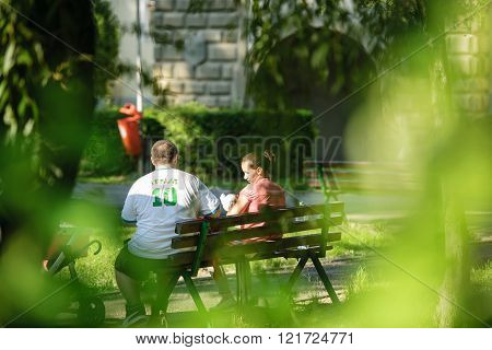 BRASOV ROMANIA - JUL 5 2015: Candid view of young family with one children in park inthe center of the Romanian city of Brasov