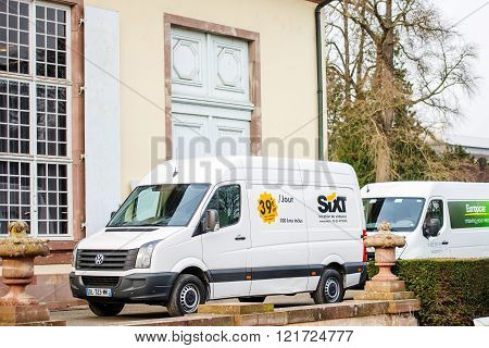 STRASBOURG FRANCE - FEBRUARY 18 2016: Sixt and Europcar vans in front of old building - delivering goods. Sixt and Europcar ar the biggest renting cars company in the EMEA region with thousands of cars intheir fleets