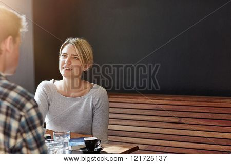 Young blonde woman with short bobbed hair sitting in a modern cafe on a wooden bench with a dark grey wall behind her, having coffee with a male companion.